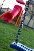 children's playground in the grass with swing and slide