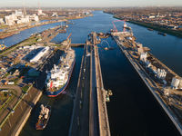 Aerial drone view of a big sluice sea port going towards Amsterdam near Ijmuiden and Velsen Noord a ship going thorugh the largest sluice in the world
