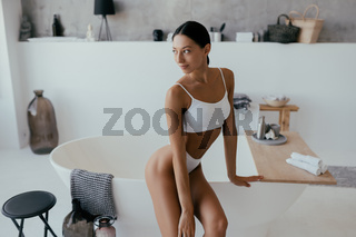 Attractive woman in lingerie posing near the bath