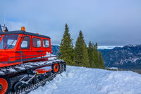 Red Snowcat and Cloudy Sky Over Winter Mountains