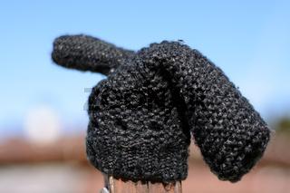 schwarzer Handschuh einsam auf Holzpflock - Tiefenunschärfe Fäustling