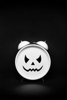 Retro Clock with scary face on dark background