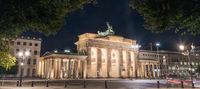 Brandenburg Gate at night with a treetop as a frame
