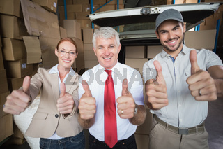Warehouse managers and delivery driver smiling at camera
