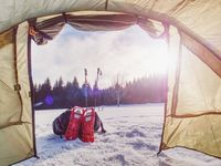 Light tent set on snow in winter forest in mountains