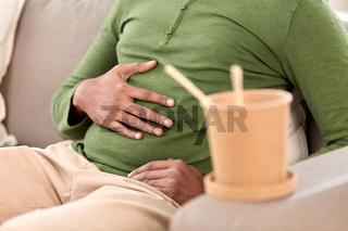 close up of overeaten man and cup of takeaway food