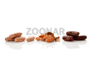 Fresh roasted cocoa beans and peels isolated on white background.