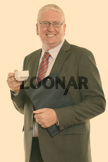 Studio shot of happy mature businessman smiling while holding clipboard and coffee cup