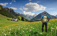 Hiker with Backpack standing on Flower meadow. Snow covered mountains and traditional house. Bavaria, Alps, Oberstdorf, Allgau, Germany.