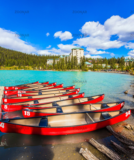 Red canoes are moored to the coast
