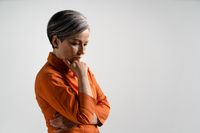 Pensive mature grey haired woman in orange shirt looks down. Pretty mid aged grey haired woman in orange shirt isolated on grey background