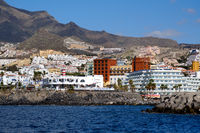 Tenerife, Spain - October 15, 2019: Waterside distant view touristic place Los Cristianos coastline, resort town, situated on south coast of Canary Islands, Spain