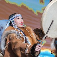 Woman in national clothing indigenous inhabitants Kamchatka dancing with tambourine. Concert, celebration national Koryak holiday Day of Seal Hololo