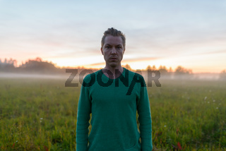 Young handsome man against grass field with fog in the break of dawn