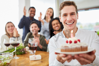 Junger Mann übergibt Kuchen mit Kerze zum Geburtstag
