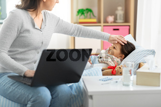ill daughter and mother with laptop at home