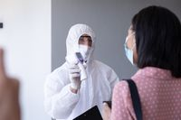 Health worker wearing protective clothes showing temperature to businesswoman