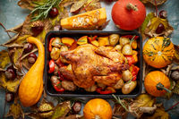 Roasted chicken or turkey garnished with pumpkins, pepper and potatoes. Served on a rustic table