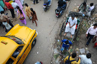 Kolkata, India, Street scene with pedestrians, rickshaw and yellow taxi