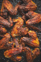 Grilled chicken wings in spices in black metal baking tray on stone table. Top view