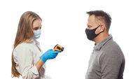 Looking at non-contact thermometer nurse testing employee's or patients body temperature wearing a medical face mask. Sad man wearing reusable face mask isolated on white background