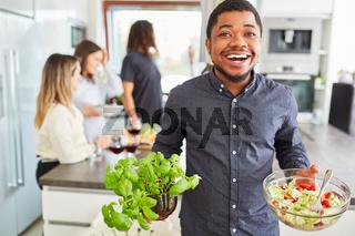 Mann mit Salat und Basilikum beim Vorbereiten für das Mittagessen