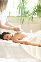 Masseuse doing procedure on back of client