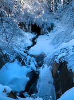 Alpine mountain snowy winter forest with snowdrifts and frozen small stream