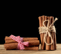 tied bunch of brown cinnamon sticks on a brown wooden background