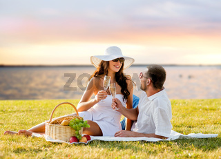 happy couple drinking champagne on picnic