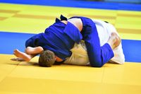 Two judoka in kimono compete on the tatami