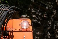 Bulldozer headlight, huge orange powerful construction machine