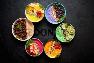 Various healthy fresh smoothies or yogurts in bowls. With strawberries, kiwi, chia, blackberries