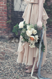 Woman in boho dress holding lush bouquet