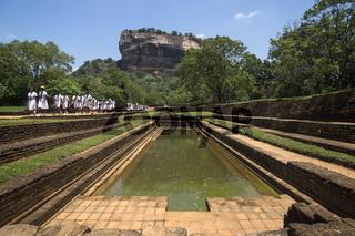 Sigiriya, Sri Lanka - March 23 2017: Students of a school class in white uniforms on a pathway at Lions Rock