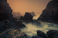 Sea fog and sunrise on sharp craggy coastline