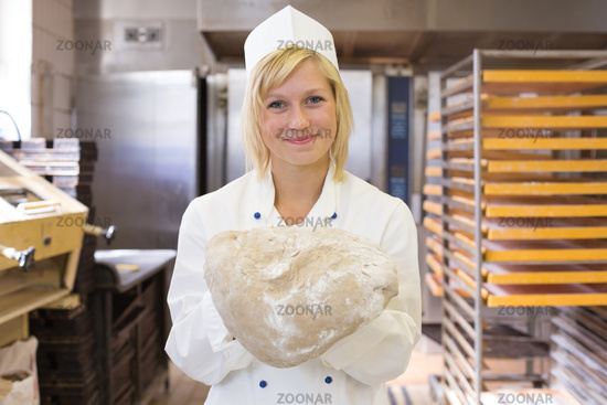 Baker with bread dough in bakery