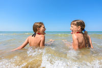 Children sit together in shallow water and show each other tongue