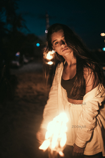 Young woman with torchlight on the beach at night