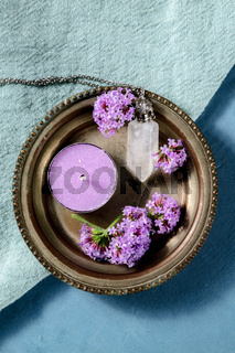 Verbena flowers, candle, and a crystal vial for essential oils, overhead shot