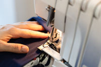 tailor overcasting the edge of fabric on overlock