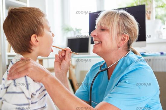 Pediatrician examines child with tonsillitis
