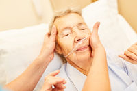 Alte Frau mit Sauerstoffbrille im Pflegeheim