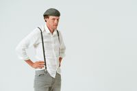 Portrait of hipster man dressed in white shirt and grey jeans and wool cap isolated on white background. Copy space at right side