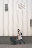 Young woman wearing protection face mask against coronavirus COVID-2019, novel coronavirus 2019-nCoV pushing a shopping cart on supermarket department store wall background. Concept of coronavirus quarantine and pandemic.