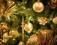 Christmas tree with gold bauble ornaments. Decorated Christmas tree closeup. Balls and illuminated garland with flashlights. New Year baubles macro photo with bokeh. Winter holiday light decoration