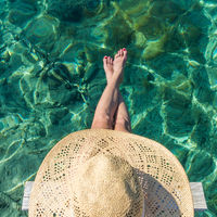 Graphic image of top down view of woman wearing big summer sun hat relaxing on small wooden pier by clear turquoise sea