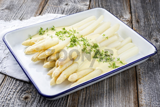 Traditional steamed white asparagus with sauce hollandaise and herbs as closeup in an enamel tray on a wooden board