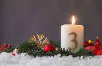 Candle of the third Advent burns, fir branches and Christmas tree balls in the snow