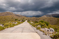 The gold's road, San Luis, Argentina, which climbs steppe mountains. Seen from below while a heavy storm is coming